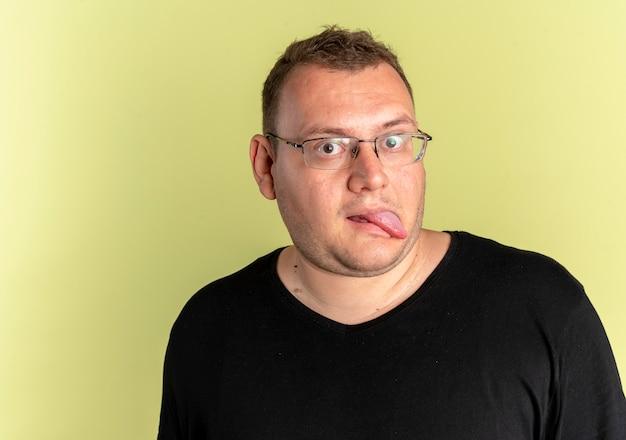 光の上に舌を突き出している黒いtシャツを着ている眼鏡の面白い太りすぎの男 無料写真