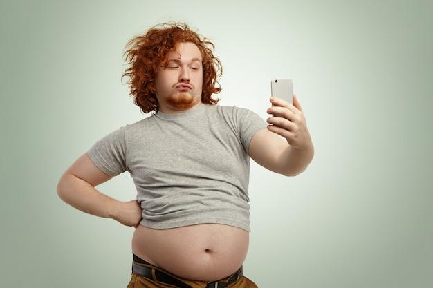 Uomo grassoccio in sovrappeso divertente con le labbra di anatra che indossa la maglietta sottodimensionata con la pancia che pende dai pantaloni Foto Gratuite