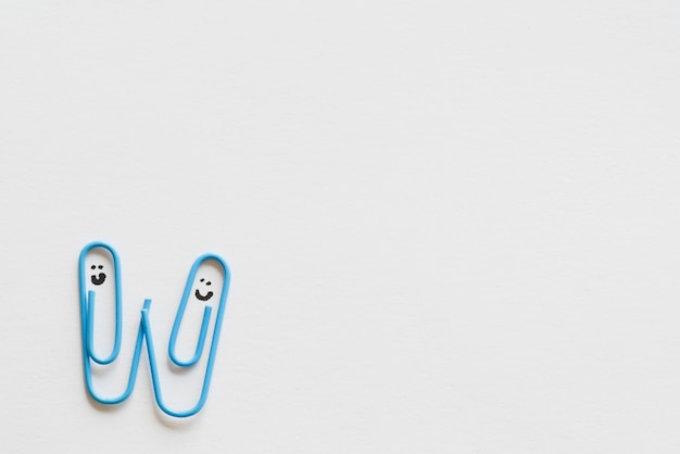 Funny paper clips on paper Free Photo