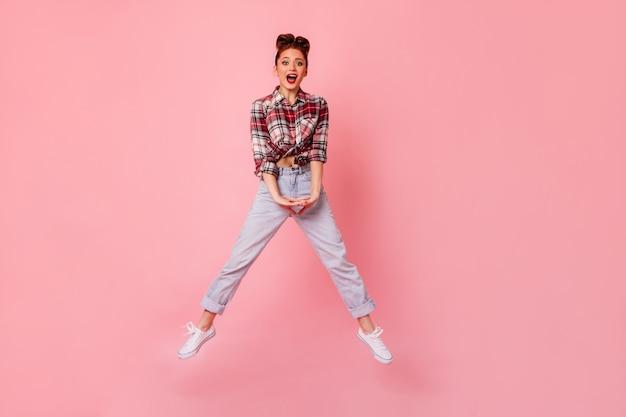 ジャンプしてカメラを見ているブルージーンズの面白いピンナップガール。ピンクの空間で踊る市松模様のシャツを着た若い女性の全身像。 無料写真