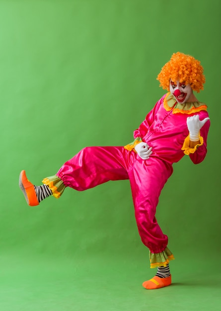 Funny playful clown in orange wig imitating playing guitar. Premium Photo