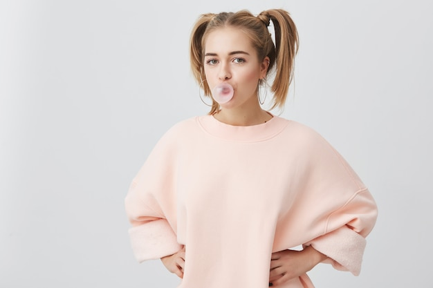 Смешная игривая белокурая девушка-подросток с двумя хвостиками в розовом свитере с длинными рукавами, с радостным выражением лица, с пузырем жевательной резинки во рту, изолированная Бесплатные Фотографии