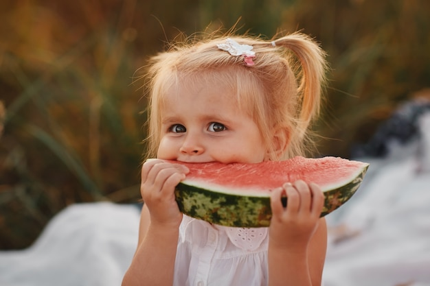 Funny portrait of an incredibly beautiful red-haired little girl eating watermelon, healthy fruit snack, adorable toddler child with curly hair playing in a sunny garden on a hot summer day. portrait Premium Photo