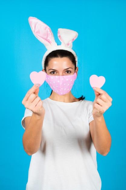 Забавный портрет женщины в защитной маске с ушками кролика и сердечком на синем Premium Фотографии