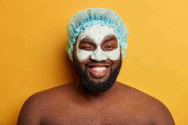 Смешной позитивный темнокожий мужчина подмигивает, после душа наносит антивозрастную глиняную маску для лица, носит защитный головной убор Бесплатные Фотографии