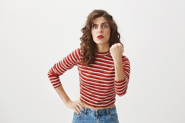 Смешная симпатичная женщина угрожает вам кулаком, ругает или предупреждает Бесплатные Фотографии