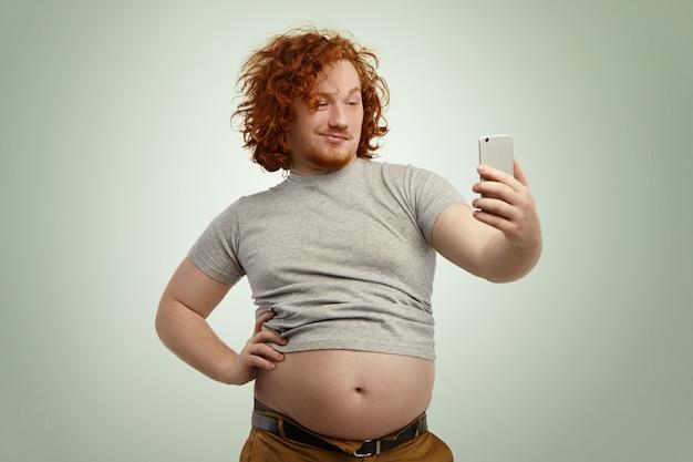 Забавный рыжий мужчина с избыточным весом пытается выглядеть привлекательно и сексуально, держа руку на талии, принимая селфи с электронным устройством, расстегнул ремень на штанах из-за торчащего толстого живота Бесплатные Фотографии