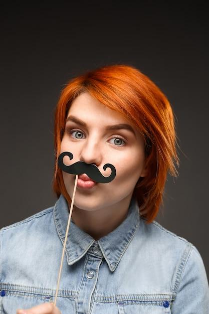 面白い赤毛の女性は偽の口ひげを着る 無料写真