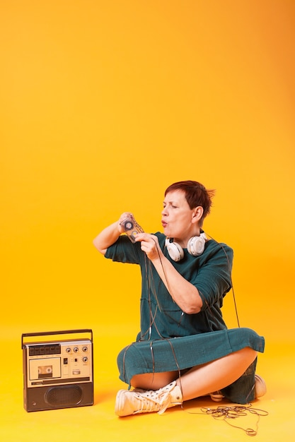 Funny senior woman covered with cassette tape Free Photo