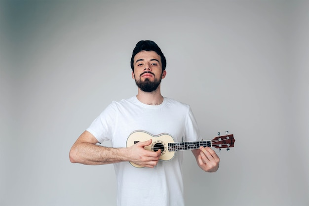 Funny serious guy with ukulele in hands playing Premium Photo