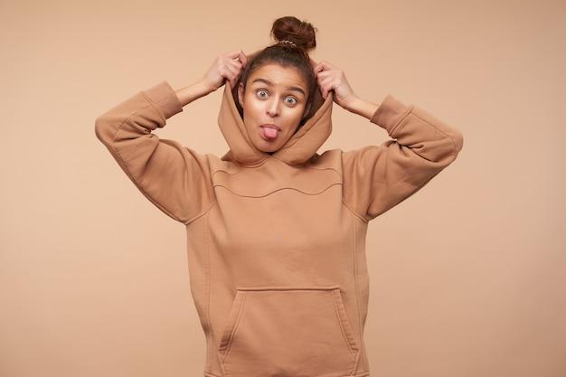 베이지 색 벽에 고립 된 그녀의 후드를 복용하는 동안 앞에 유쾌하게 혀를 보여주는 롤빵 헤어 스타일을 가진 젊은 사랑스러운 갈색 머리 아가씨의 재미있는 샷 무료 사진