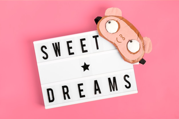Funny sleep mask and lightbox with  quote sweet dreams on pink background flat lay Premium Photo