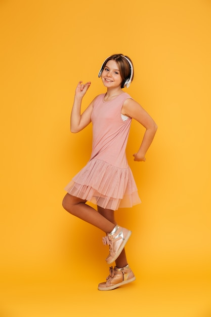 Funny smiling girl in headphones dancing isolated over yellow Free Photo
