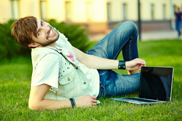 Funny smiling hipster handsome man guy in stylish summer cloth in the street sitting on grass in the park with notebook Free Photo