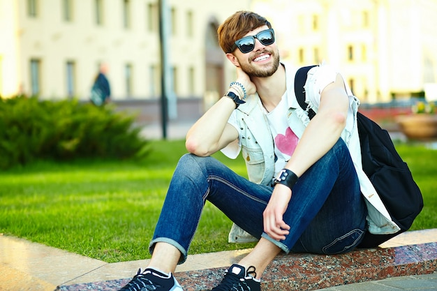 Funny smiling hipster handsome man guy in stylish summer cloth in the street sitting on grass in the park Free Photo