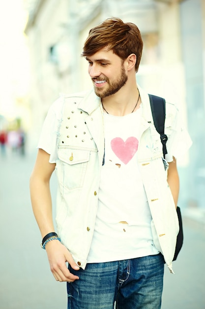 Funny smiling hipster handsome man guy in stylish summer cloth in the street Free Photo