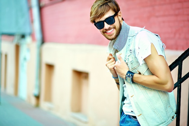 Funny smiling hipster handsome man guy in stylish summer clothes posing in the street Free Photo