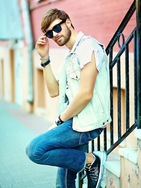 Funny smiling hipster handsome man guy in stylish summer clothes in the street posing near colorful bright wall in sunglasses Free Photo