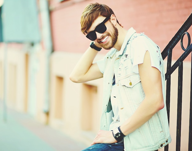 Funny smiling hipster handsome man guy in stylish summer clothes in the street in sunglasses Free Photo