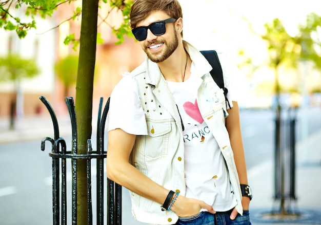 Funny smiling hipster handsome man guy in stylish summer clothes walking in the street posing  in sunglasses Free Photo