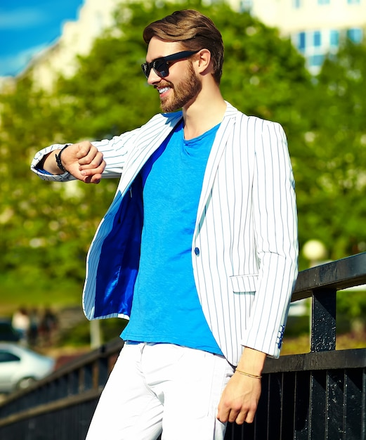 Funny smiling hipster handsome man in stylish summer white suit posing on street in sunglasses, looking at watches Free Photo