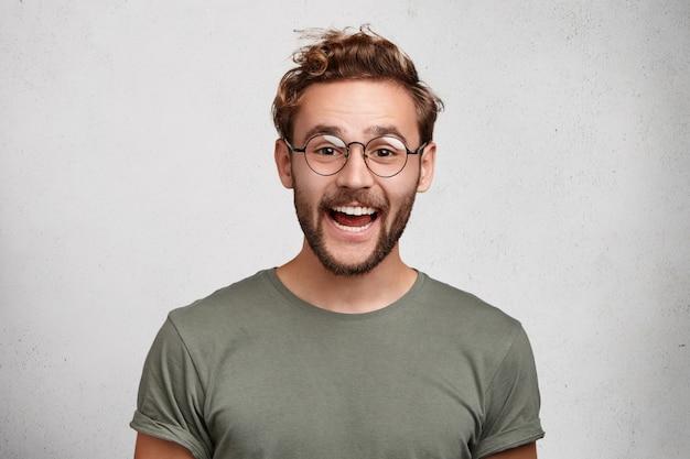 Забавный улыбающийся небритый вонючий мужчина носит круглые очки и повседневную одежду, радуясь Бесплатные Фотографии