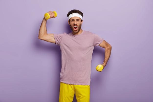 재미있는 운동가는 덤벨로 팔을 들고 감정적으로 외치고 강하고 스포티하며 보라색 티셔츠와 노란색 반바지를 입고 실내에 서 있습니다. 남자는 체육관에서 운동하고 운동을합니다. 보디 빌딩 무료 사진