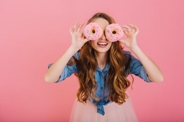 Divertente ragazza alla moda in abiti alla moda scherza con deliziose ciambelle che ha comprato al panificio per il tè. ritratto di graziosa giovane donna riccia in posa con dolci isolati su sfondo rosa Foto Gratuite