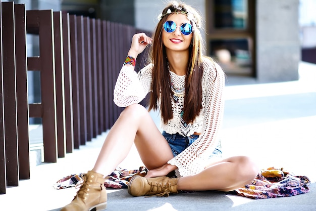 Funny stylish sexy smiling beautiful young hippie woman model in summer white hipster clothes posing in the street Free Photo
