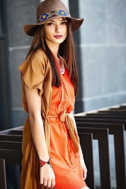 Funny stylish sexy smiling beautiful young hippy woman model in summer bright hipster clothes dress in the street in hat Free Photo