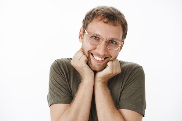 Забавный трогательный и симпатичный взрослый кавказский мужчина в очках с щетиной, опирающийся на ладони и улыбающийся с девчачьим выражением лица, довольный и милый, действующий женственно Бесплатные Фотографии