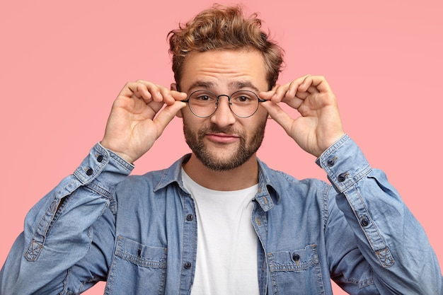 Funny unshaven man has thick beard, keeps both hands on rim of glasses, has curious look while listens something interesting Free Photo