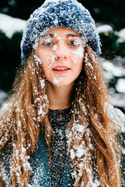 Funny winter portrait of beautiful long haired brunette girl with her face and hair covered in snow. Premium Photo