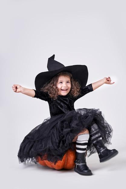Смешная ведьма девушка в шляпе, сидя на тыкве. Premium Фотографии