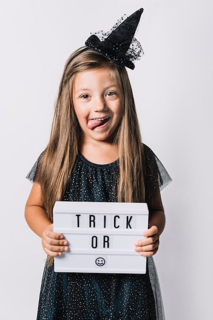 Funny witch holding board with writing Free Photo