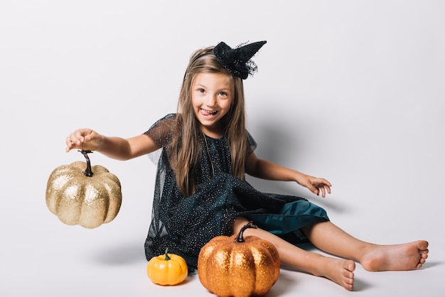 Funny witch playing with pumpkins Free Photo