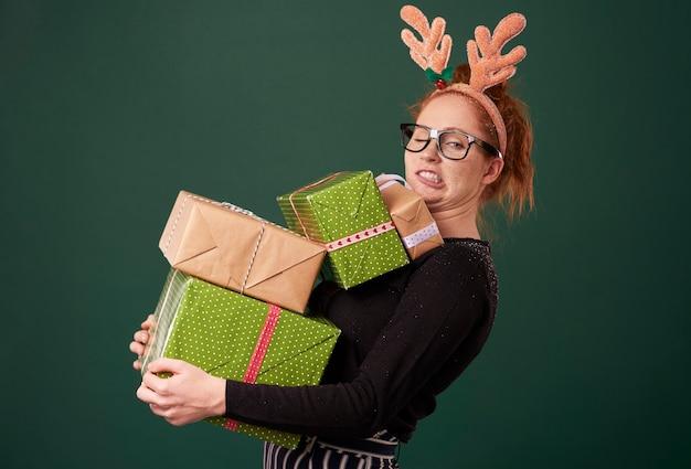크리스마스 선물의 스택을 들고 재미있는 여자 무료 사진