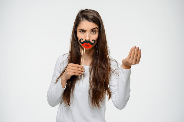 Funny woman grimacing in fake moustache and lips Free Photo