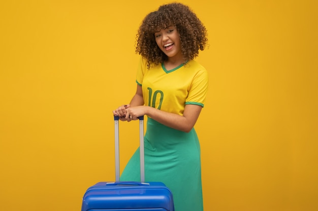 Funny woman holding a heavy travel bag Premium Photo