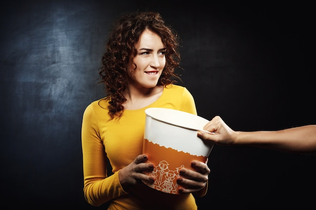 Funny woman striving for popcorn with friends while watching movie Free Photo