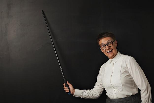 丸いメガネで愚かな顔を笑顔で面白い女教師は、黒のチョークボードに彼女のポインターで幸せに何かを示しています 無料写真