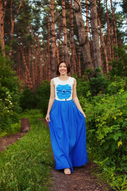 Funny woman walking in the forest. summer. the concept of lifestyle, nature and travel. Premium Photo