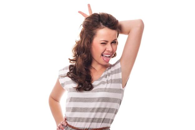 舌を突き出している角を持つ面白い女性 無料写真
