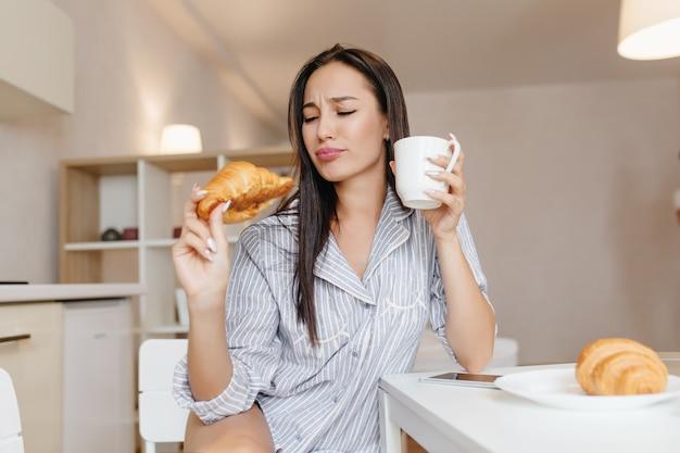 Donna divertente con capelli neri dritti che mangia croissant durante la colazione in appartamenti accoglienti Foto Gratuite