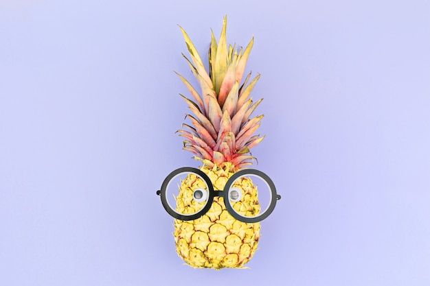 Funny yellow pineapple face with glasses on violet. Premium Photo