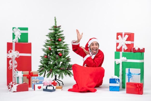 재미 있은 젊은 성인 선물 산타 클로스로 옷을 입고 흰색 배경 위에 가리키는 바닥에 앉아 장식 된 크리스마스 트리 무료 사진