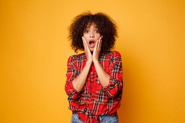面白い若いアフリカ女性がオレンジ色の背景に分離されたポーズします。驚きの顔。スタジオ撮影。 無料写真