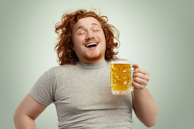 Funny young caucasian male feeling happy and relaxed, anticipating fresh cold beer in his hands after hard working day, closing eyes in enjoyment. bearded overweight redhead man drinking lager Free Photo