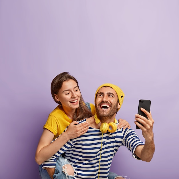 Смешная молодая пара делает селфи на смартфоне, наслаждается поездкой на спине, имеет счастливые выражения лица, милая женщина обнимает парня со спины, изолированные на фиолетовом фоне. люди Бесплатные Фотографии