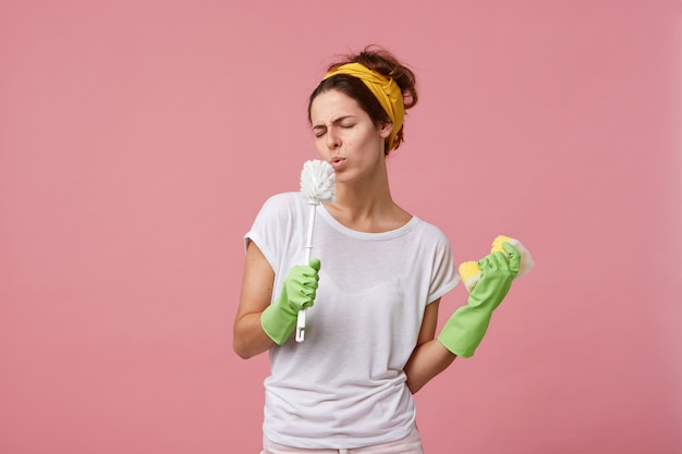 ヘッドバンド、カジュアルなtシャツ、緑のゴム手袋を身に着けている自宅でのクリーニングプロセスを楽しんでいる面白い若いヨーロッパの主婦 無料写真